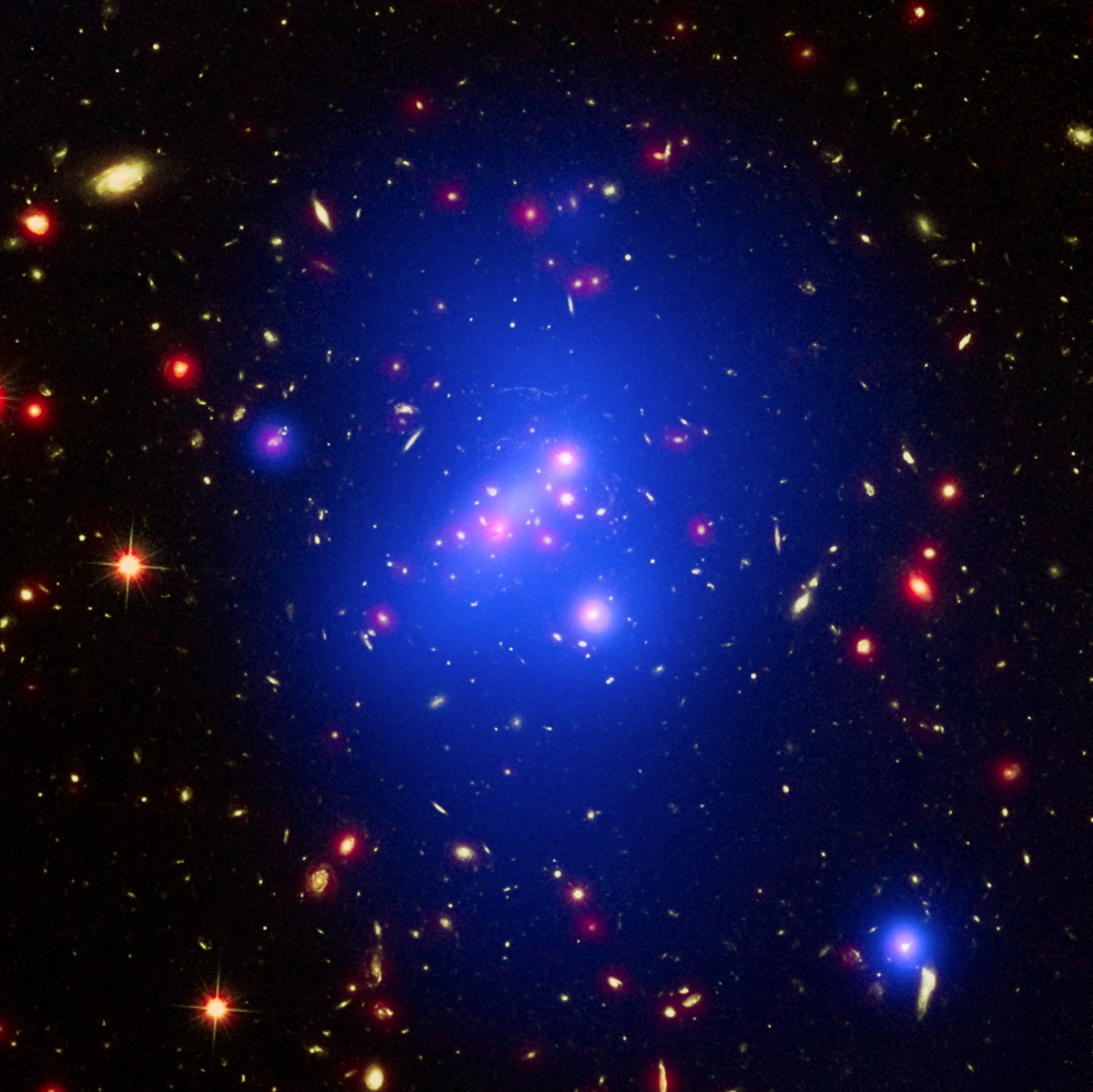 This image of the massive galactic cluster IDCS 1426 combines data taken by three major NASA telescopes. The off-center core of X-rays is shown in blue-white near the middle of the cluster, and was captured by Chandra. Visible light from the Hubble Space Telescope is green, and infrared light from Spitzer is shown in red.